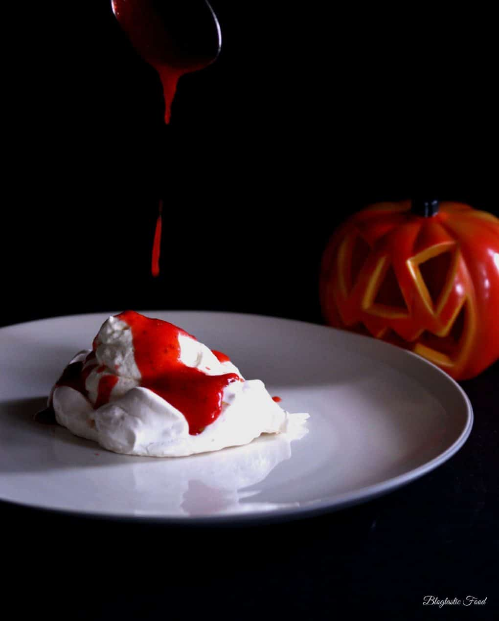 A photo of strawberry coulis being spooned over meringue on a plate.