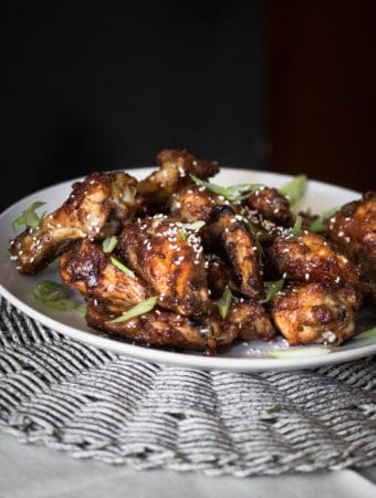 A dark moody photo of spiced and glazed chicken wings.