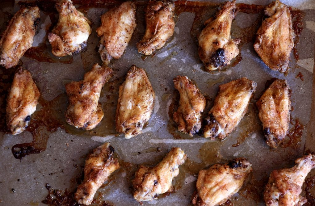 A photo of cooked chicken wings on a tray that have just come out of the oven.