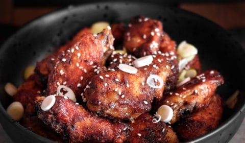 Honey soy mustard chicken wings in a bowl garnished with spring onions.
