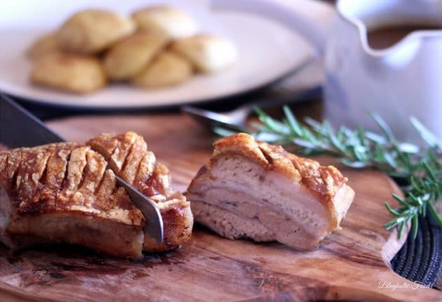 A bread knife slicing into a piece of roasted pork belly.
