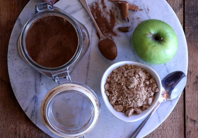 An overhead photo of cinnamon, brown sugar and an apple.