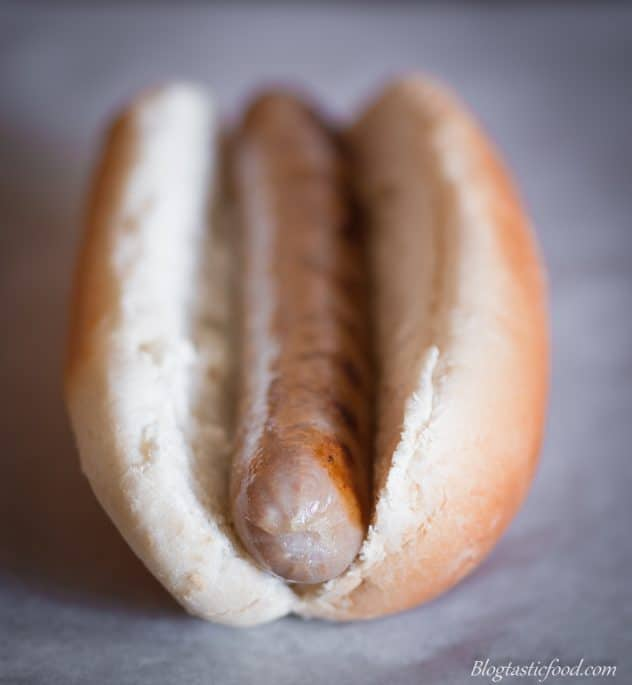 A photo of a bun with a sausage in it.