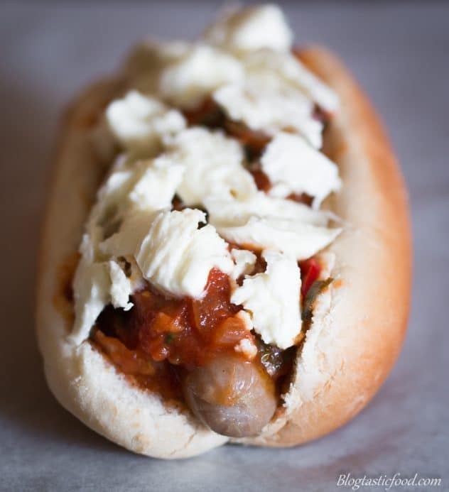 A photo of a hot dog with tomato sauce and raw mozzarella cheese on top.