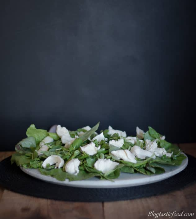 Salad leaves, asparagus and fresh mozzarella served on a marble platter.