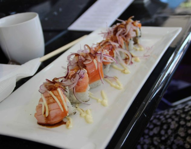 A platter of seared salmon sushi nigiri topped with thinly sliced red onions.
