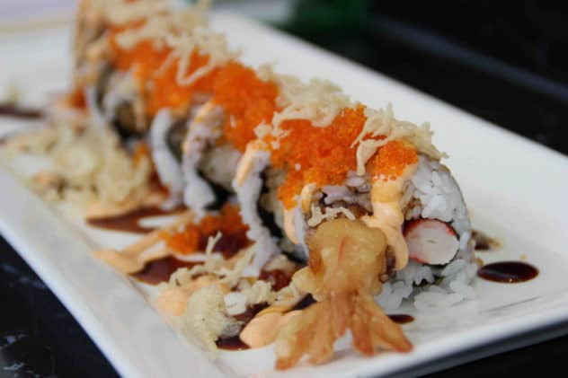 A platter of tempura prawn filled sushi rolled topped with caviar and spicy mayonnaise.