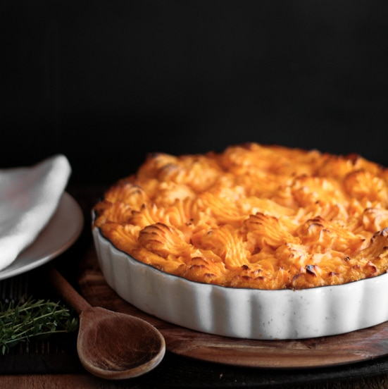 A photo of potato and sweet potato shepherds pie served in a pie dish.