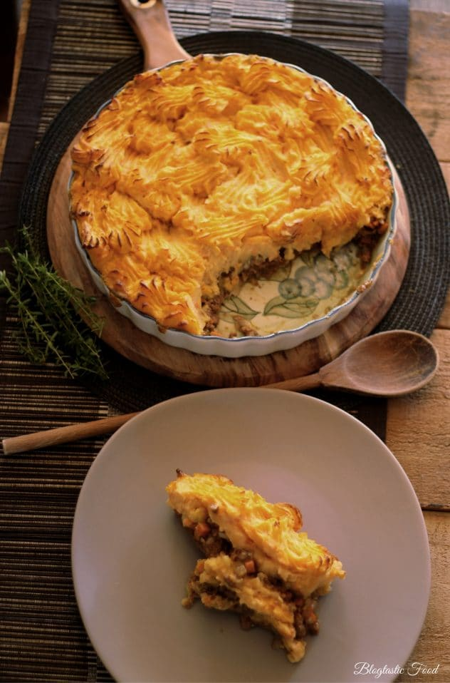 A portion of shepherds pie scooped from a pie dish onto a plate.