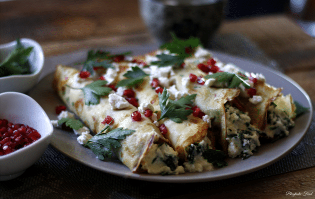 A contrast image of spinach and ricotta rolled savory crepes.