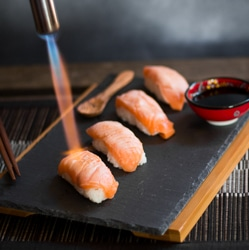 Someone using a blowtorch to sear the salmon sushi nigiri on a platter with a mini bowl of soy sauce.