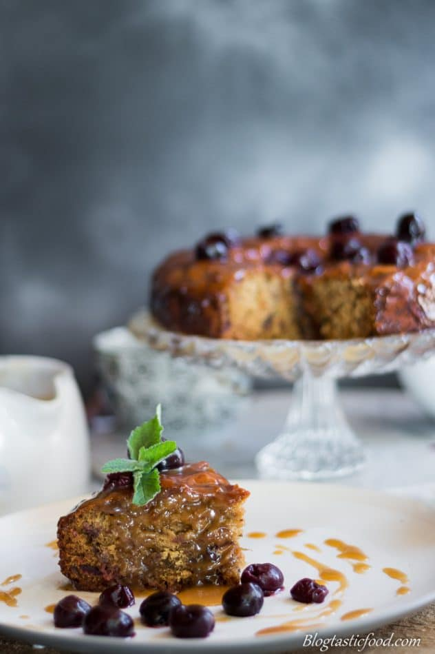 A slice of sticky date pudding with butterscotch sauce, garnished with a sprig of mind and cherries.