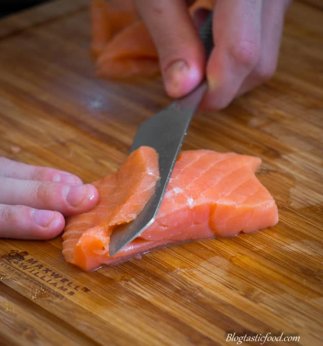 A fresh fillet of salmon being thinly sliced on a board.