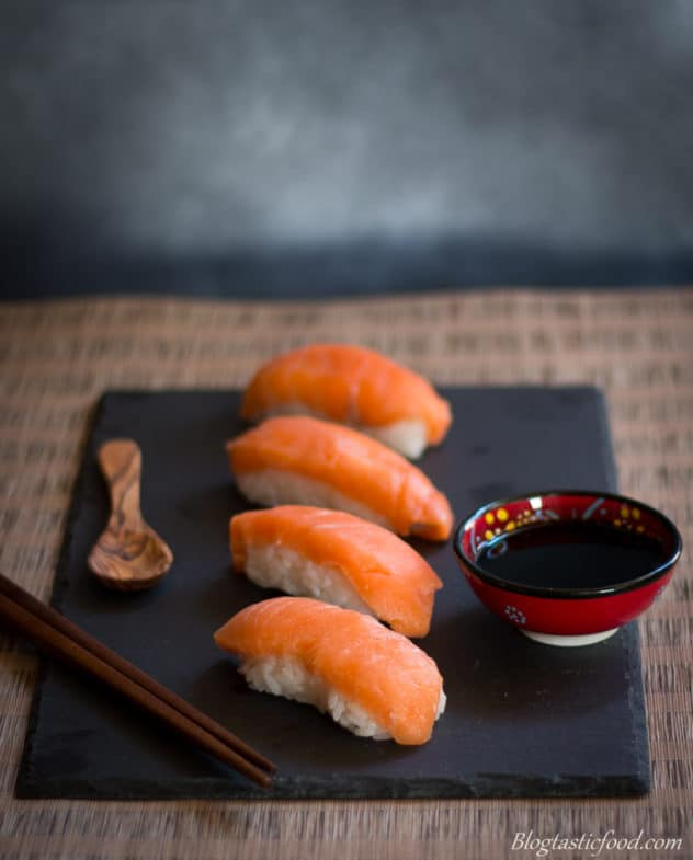 A platter of salmon sushi nigiri served with a mini bowl of say sauce.