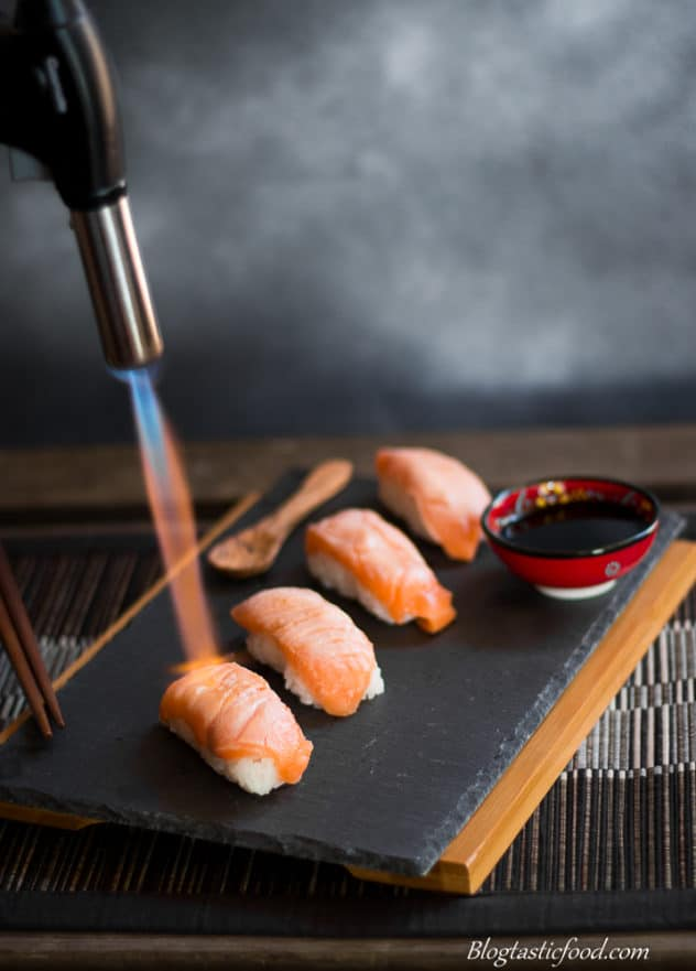 Someone using a blowtorch to sear fresh salmon sushi nigiri on a platter.
