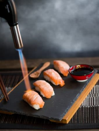 Someone using a blowtorch to sear the salmon on the sushi nigiri.