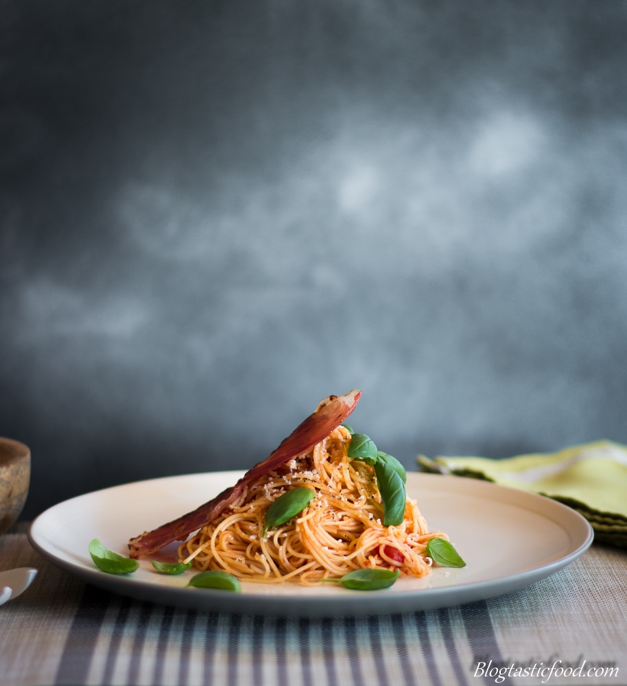 An eye level shot of angel hair napolitana pasta garnished with basil and a piece of crispy prosciutto.