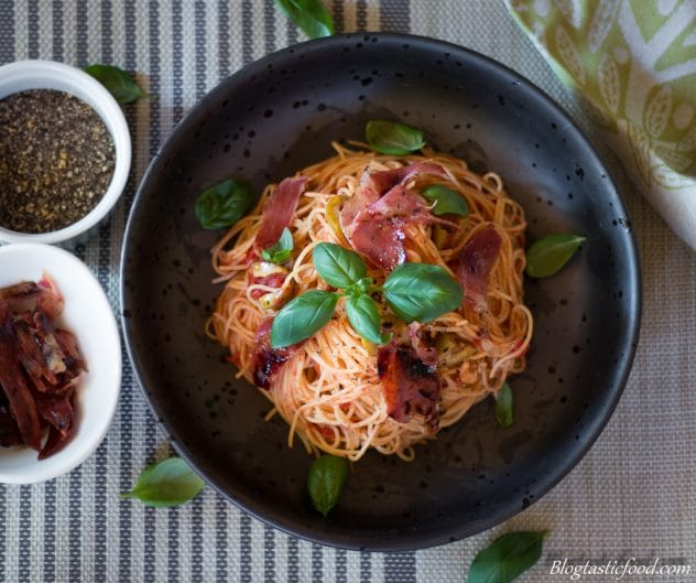 An overhead photo of angel hair pasta with crispy prosciutto in a bowl.