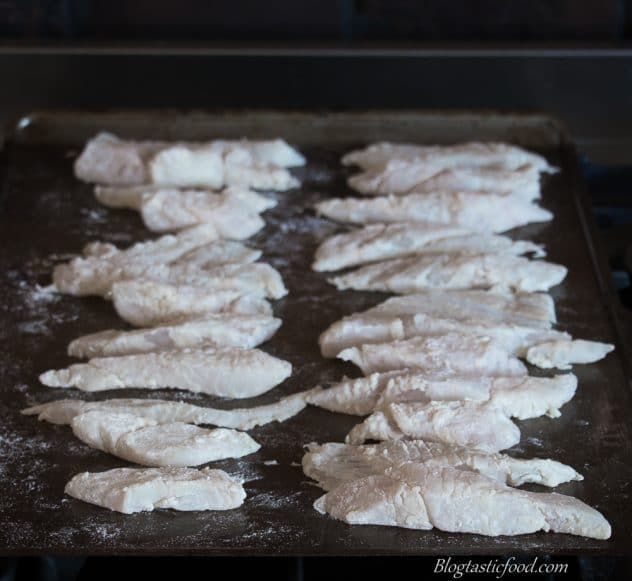 Raw, flour coated sliced of fish lined up neatly on a tray.