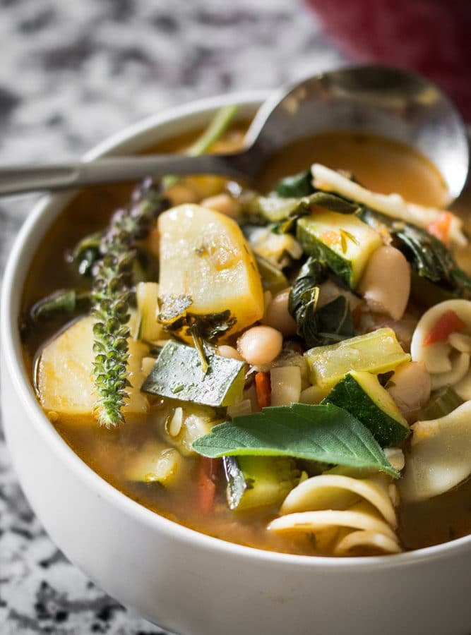 A moody, contrast photo of minestrone soup garnished with Greek basil.