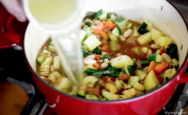 A photo of stock being added to leftover minestrone soup.
