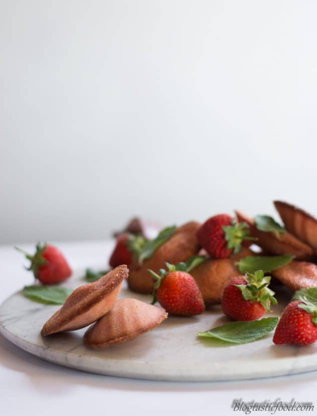 Strawberry madeleines and strawberries served on a marble platter.