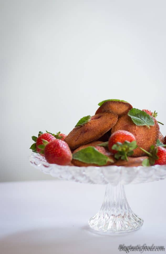 Fresh strawberries and strawberry madeleines served on a cake stand.