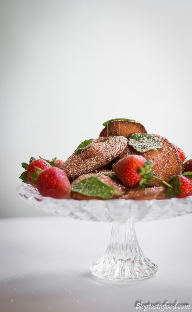Strawberry madeleines and strawberries being dusted with icing sugar.