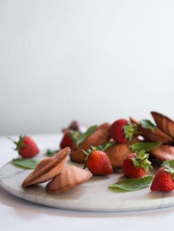 A photo of pink strawberry madeleines garnished with mint.