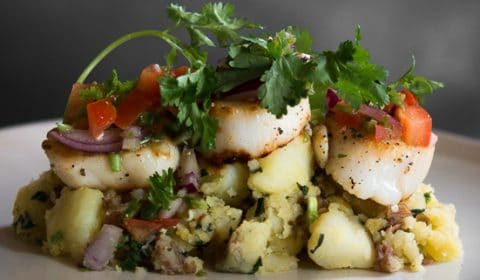 A photo of a seared scallop dish served with salsa and crushed potatoes.