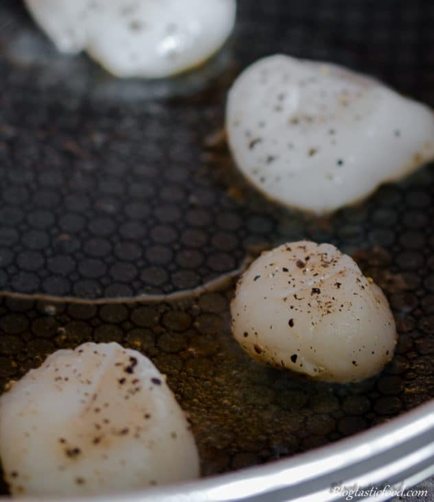 A photo of seasoned scallops getting seared in a non-stick pan.