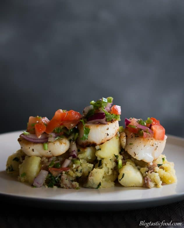 Fresh salsa, seared scallops and crushed potatoes on a white plate.