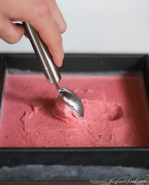Someone using an ice-cream scoop to scoop out some strawberry and vodka ice-cream out of a tin.