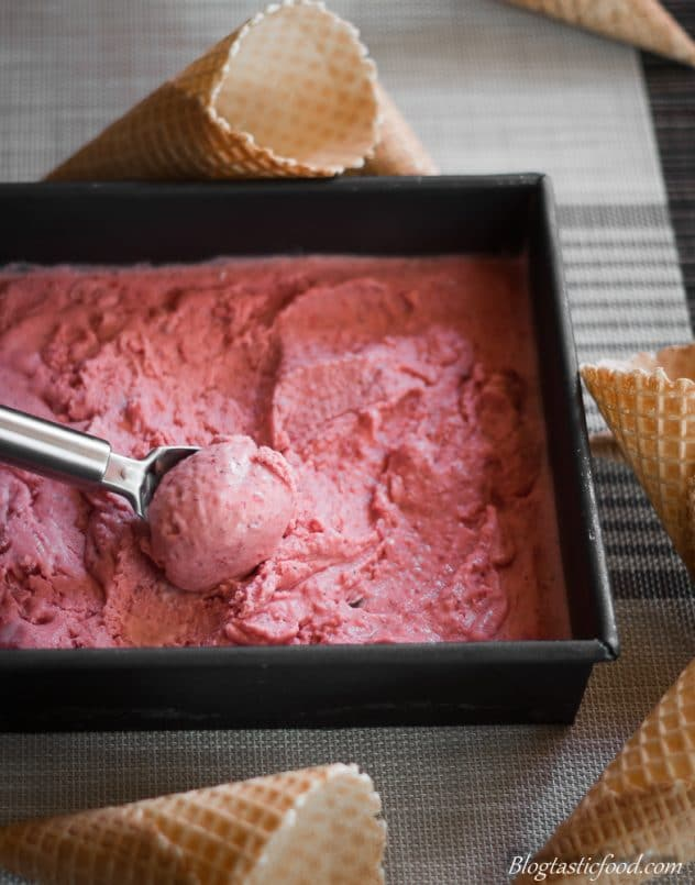 A tin filled with strawberry and vodka ice-cream with a portion being scooped out.