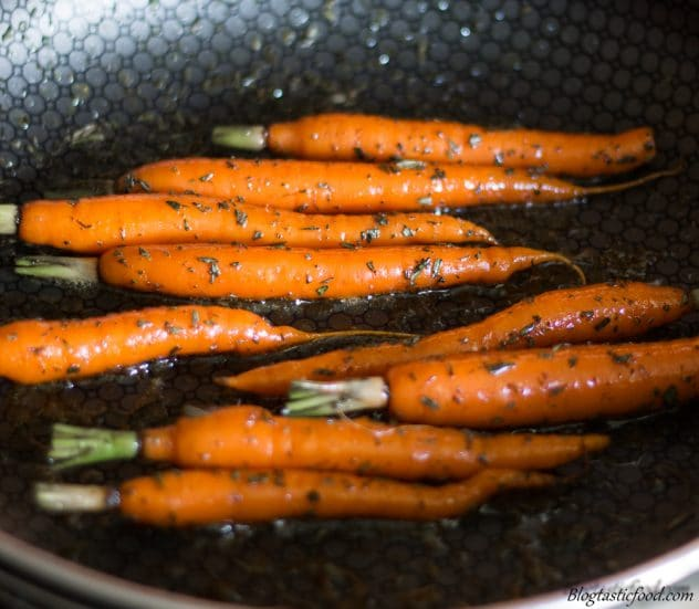 Baby Carrots being tossed through rosemary, butter and honey in a pan.