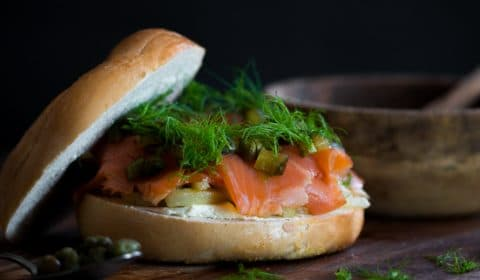 A smoked trout and fennel filled bagel burger served on a board.