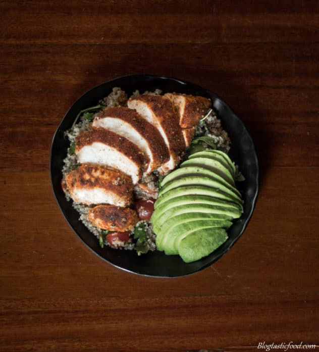 Sliced Cajun chicken and avocado over quinoa salad served on a black plate.