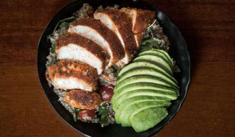 An overhead photo of quinoa salad topped with Cajun chicken and avocado.
