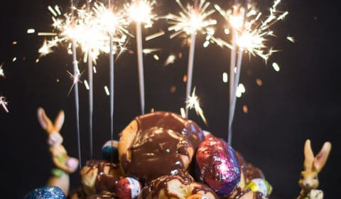 A ountain of chocolate profiteroles with lighting sparkles on top.
