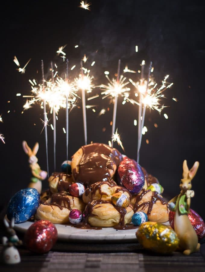 A mountain of chocolate profiteroles with sparkled lighting up on top.