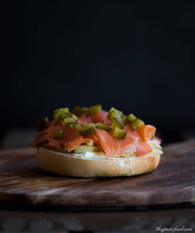 The bottom half of a bagel bun which has sliced fennel, smoked trout and diced gherkins on top.