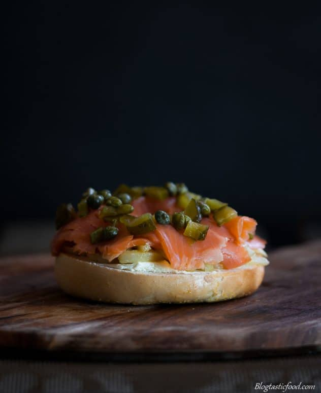 Chopped gherkins, capers, smoked trout and fennel on the bottom half of a bagel bun.