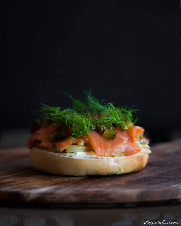 The bottom half of a bagel burger with fennel, smoked trout, gherkins and capers on top garnished with fennel tips.