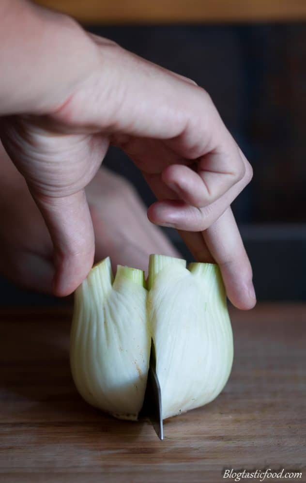 Some using a knife to cut a bulb of fennel in half.