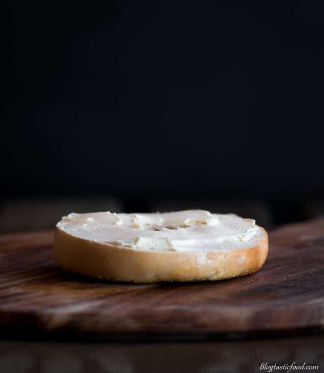 A picture of half a bagel bun with cream cheese spread onto it.