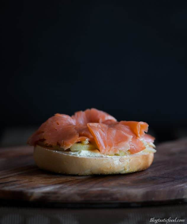 Cream cheese, pan fried fennel slices and smoked trout on half of a bagel bun.
