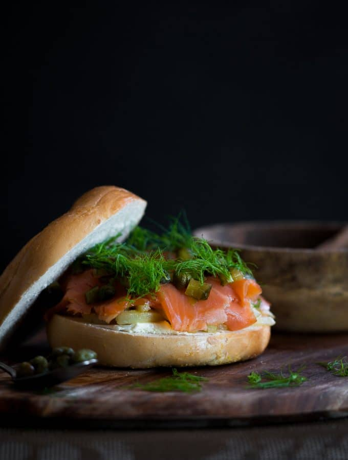A wooden board with smoked trout and fennel filled bagel burger on it and fennel tips scattered around.