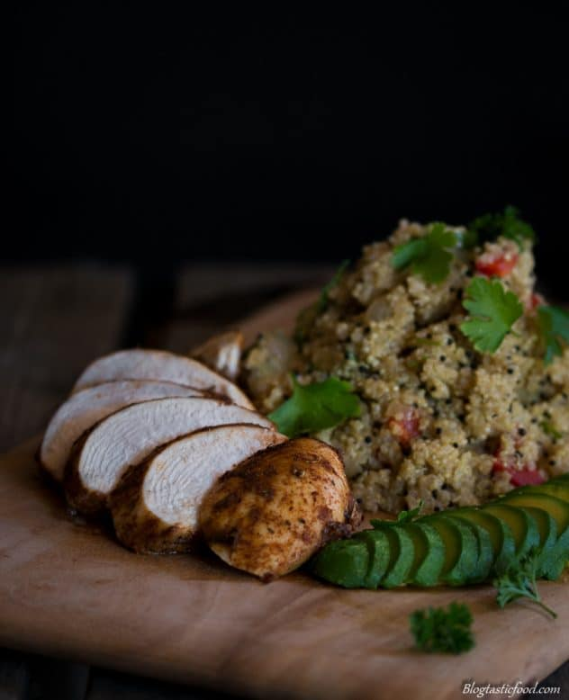 A dark moody photo of Cajun chicken served with quinoa.