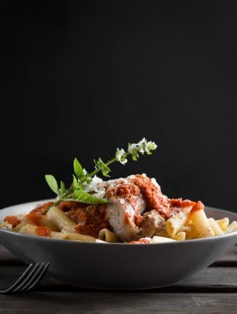 A dark, contrast photo of sausage pasta in a bowl, with tomato sauce and basil on top.