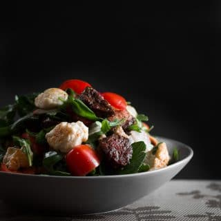 A dark, moody contrast photo of crispy chorizo and fried halloumi salad.